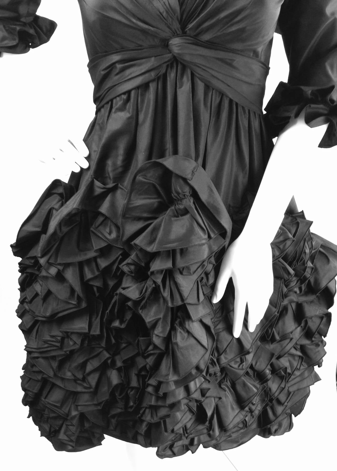 Breathtaking 1990's Oscar de la Renta Dress is meticulously constructed of Black Silk Faille. Ruffles and rosettes create wonderful texture and interest on the high low skirt accented by ruffles on the three quarter length sleeves. The cinched