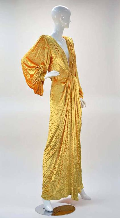 There are no words to describe this drop-dead-gorgeous, cheetah print, goldenrod yellow, deep-V, vintage bomb shell of a dress. Two clasps keep dress together hitting the breast bone, creating wonderful draping. Additionally draped sleeves give an