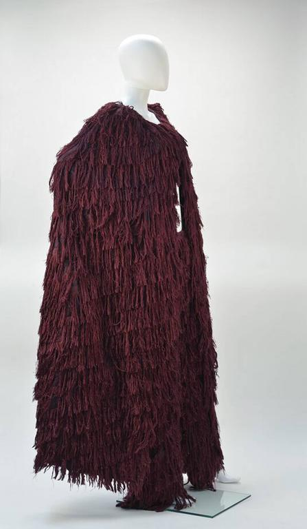 If you're looking for a statement outfit, this is definitely the one. A Mila Schon dramatic burgundy silk fringe ensemble, comprised of a burgundy silk cape with a silk fringe motif, together with a fantastic matching fringe pant.    The silk