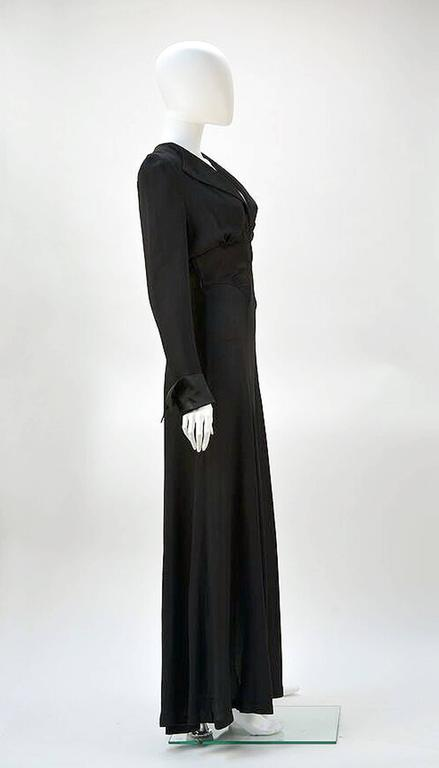 Elegant 1970's Ossie Clark for Radley black moss crepe dress. Dramatic plunging neckline enhances the appeal of this tribute to 1930's design.  Clark highlights the waistline in both the cut of the dress and the tie at back giving the illusion of