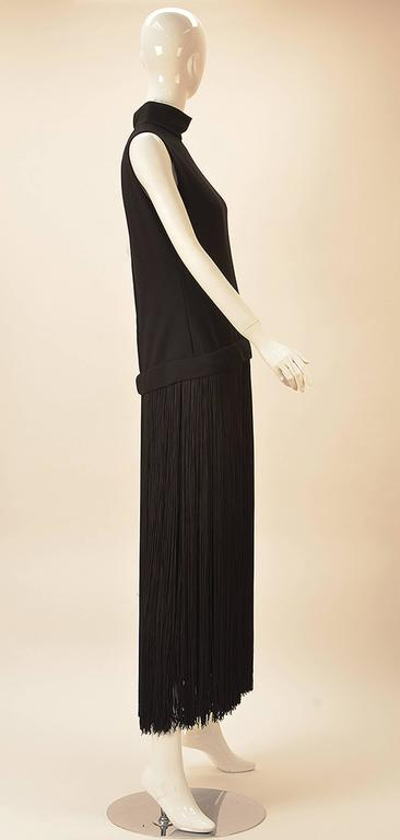 This Adele Simpson 1960's dress is spectacularly layered. The dress is long, with a black fringed under slip. Features stand up collar and drop waist. Zips in back.  This dress fully speaks for itself as depending on height is a maxi dress or of