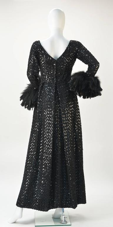 Phenomenal Lillie Rubin Collection 700 long black zigzag sequin dress with black feather cuffs. Simple ballet neckline. Empire waist with A-line skirt. Pleat at zipper back. We love this dress!  Size 2 Petite  Empire Waist: 28 inches  Wrist: