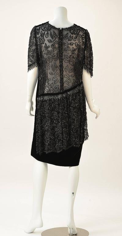 1980's does the 1920's in this Gorgeous black velvet dress with sheer back beading on tulle.  Sleeves are beaded and have bugle bead fringe -- absolutely amazing beadwork.  Sheer back to drop waist with gorgeous sheer beaded overlay down back at a
