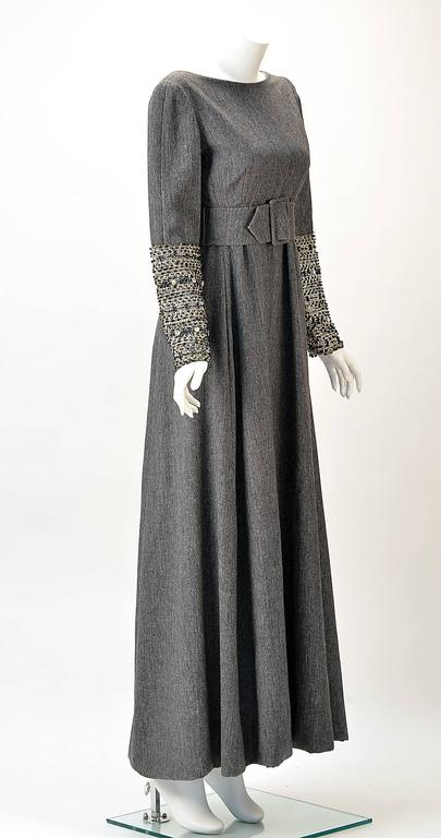 Elegant Malcolm Starr grey wool dress designer by Elinor Simmons. Dress has a low scoop back. Empire waist. Three inch Grey wool belt and buckle. Sleeve  are embellished from elbow down with silver thread and sequins, beads and rhinestones.