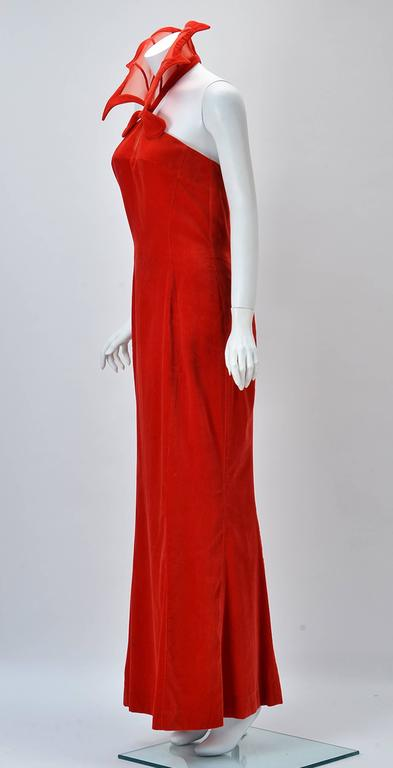 "Rare and Outstanding 1980's ""Kiss of the Spider-woman"" gown by Thierry Mugler. Dramatic red velvet fit and flare stand up collar dress. Strapless with collar attaching at front neck and velvet covered snaps at neck back. Red net keyhole at"