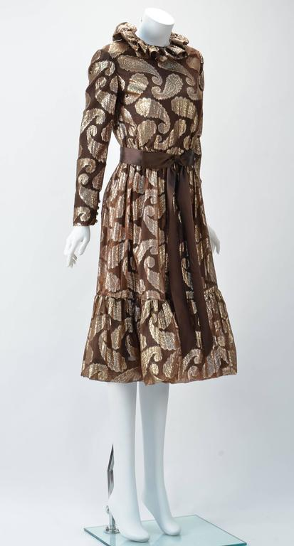 Adorable 1960s Cecil Chapman brown and gold paisley metallic dress. High ruffle collar, long sleeves with button cuffs and gathered tiered skirt gives youth to this look. Sweet brown satin ribbon belt with bow. Zips at back. Dress is interlined with