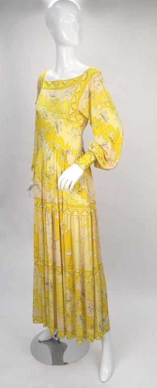 Ethereal 1970's Pucci Yellow Silk Knit print.  The Olympic inspired print boasts abstract sportsmen/women in various stages of sport. The archers' bodies are signed Emilio.   Gown has billowy bishop sleeves with cuffs that button at the wrist, and