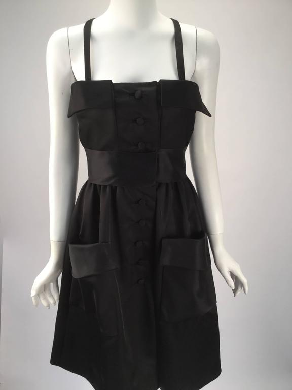 Gorgeous and uber-comfortable black satin dress with two large pockets center front. Black satin sash sits as an empire waist. The front of the dress has two fold-over flaps on the top of the dress. Eight buttons run from top until mid thigh.