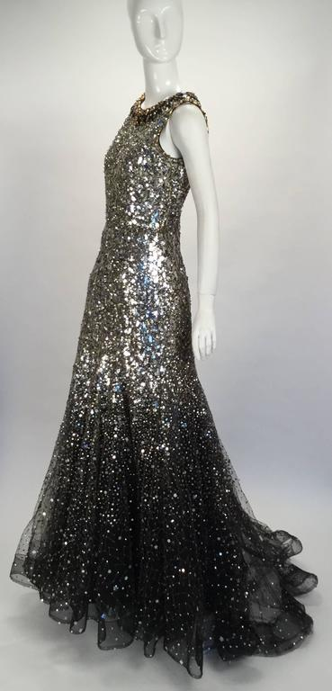 Gorgeous sequined Oscar de la Renta formal evening gown. Beautiful gold beading over mesh follows the neckline with accents of black and a rich gold color. The dress is covered in silver and gold sequins in assorted shapes and sizes. It fits closely