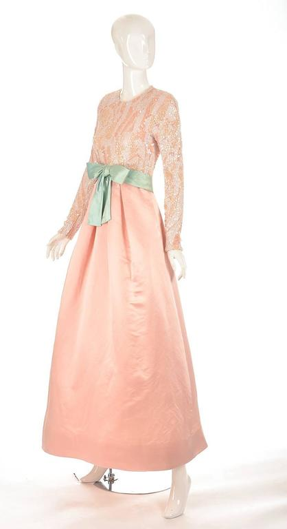 1960's Arnold Scaasi evening dress. This gorgeous blush pink silk evening dress has a pink over white bodice. White and peach colored sequins and beads fully decorate the bodice of the dress, and continue down the full length of the sleeve. The