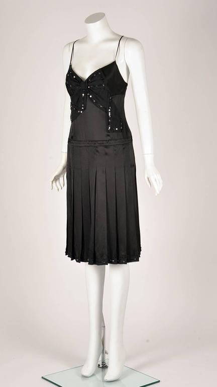 Moschino Cheap and Chic black silk spaghetti strap drop waist cocktail dress.  The dress has a black bow applique with sequin and clear rhinestone trim at center front, as well as a gently pleated skirt. The dress has a size zipper closure.