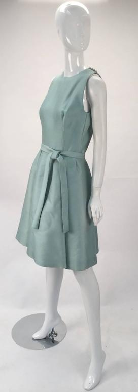 Adorable and beautiful 1960's silk seafoam green sleeveless midi dress by Geoffrey Beene. Cocktail or day wear.  Silk fabric is interlined. Self fabric belt for tying at the waist. Box pleated skirt. Bust darts. The shoulder seams have fabric