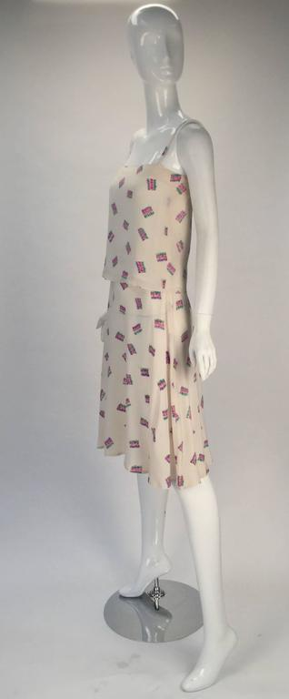 Perfect this summer and worn as an ensemble or worn as separates comes this fun 1980's Diane Von Furstenberg off white silk two piece tank top and skirt ensemble. Multicolored squiggle designs that form rectangles. The top is lined (not by