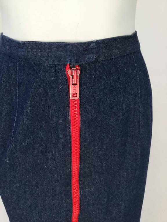 1970's faded dark wash denim midi skirt from Geoffrey Beene's 'The Beene Bag' line. Center front hook and eye closure. There is a large red metal and plastic two-way zipper that zips down center front. Red top stitching at bottom hem and by the