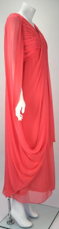 Ethereal 1970's coral colored sleeveless chiffon evening dress with draping by Victor Costa.absolutely beautiful!   The front of the dress has ruching at the bust. Chiffon fabric drapes from the front bust down to the skirt and around the back and