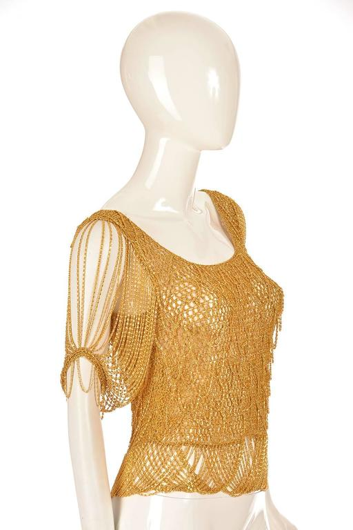 A simply fantastic top! This intricately woven gold-tone Chain and knit sweater has light chains incorporated into the diamond scallop weave. The sleeves of the top are delicate festooned chains, and the top features a scoop neck. The top slips