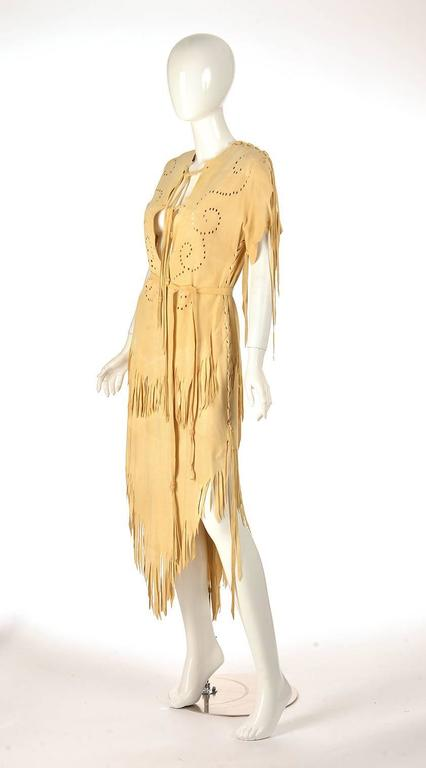 Native American leather dress with double layer fringed bottom. Dye cut swirl design on top half of dress. Dress features straps of leather, finished with beading. Sleeves are threaded together with leather. Dress slips overhead. Can be worn, used