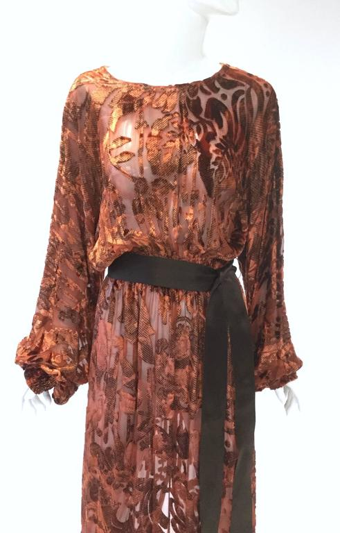 Gorgeous vintage silk Devoré dress. With its long, romantic, cuffed bishop sleeves, gathered blouson waist, and bateau boat neck, this amber-tone dress is undeniably full of bohemian charm! The dress features an intricate floral and paisley burnout