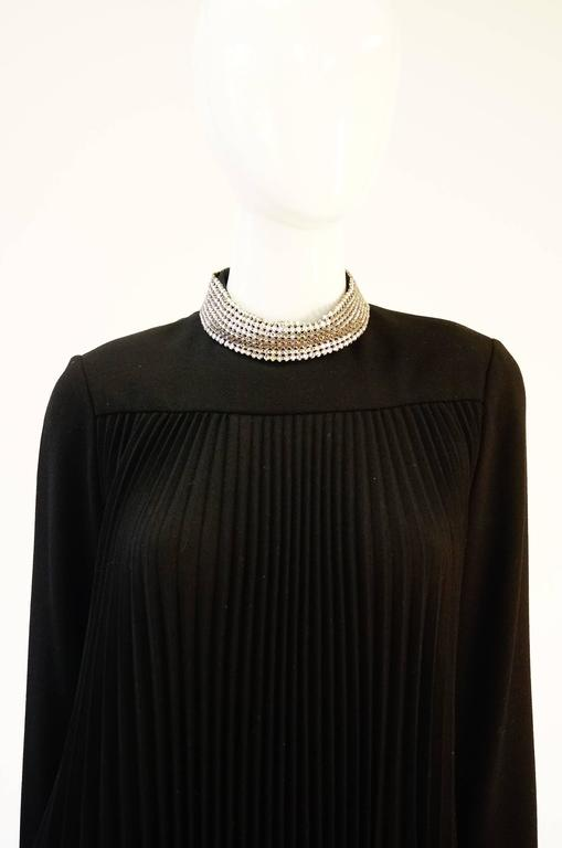 Elegant 1960s black dress by Teal Traina New York! This graceful knee length black dress has long sleeves with shimmering rhinestone cuffs, and a rhinestone collar. The dress is primarily composed of thin pleats that sway gently with every step.