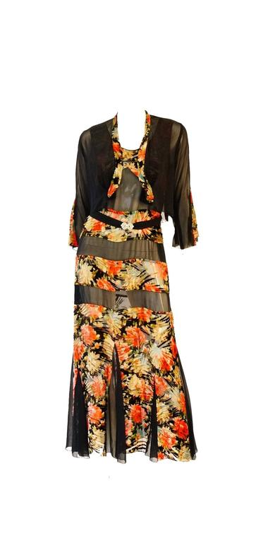 Romantic vintage maxi dress with matching bolero. This ankle length dress features alternating panels of floral rose burn out velvet in fall colors, including red, gold, blue, pink, and green, and black. The sleeveless dress has a godet skirt with