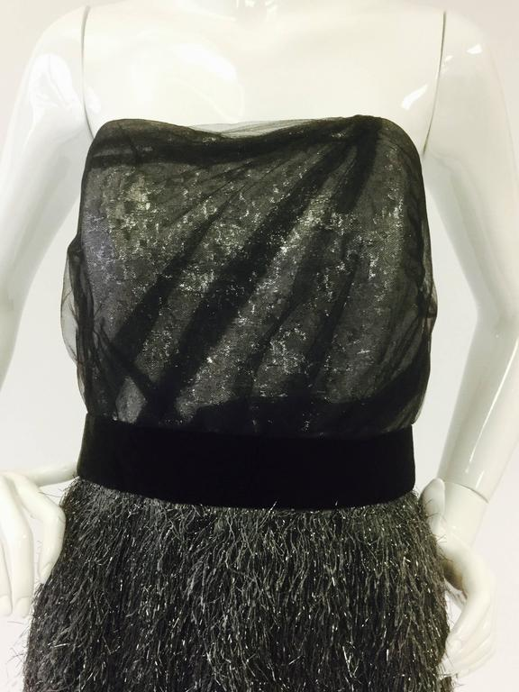 Absolutely fantastic Bill Blass cocktail dress! This dress features a metallic silver lame bodice with a sweetheart neckline. The bodice has delicate black mesh wrapped around it, highlighting the lustrous fabric below. The knee length skirt is