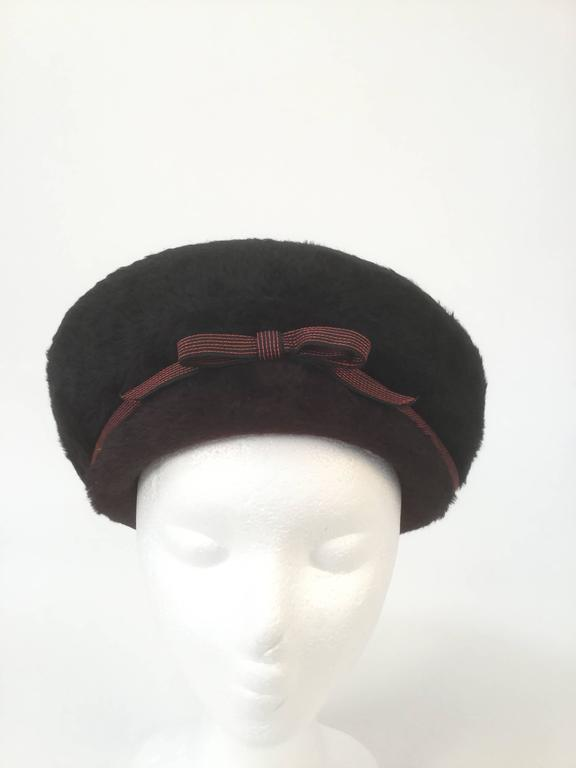 Striking red and black felt hat by Elsa Schiaparelli! This structured hat has aristocratic eastern influences, resembling a cossack hat, a Manchurian hat, and a Qing dynasty winter court official hat! The hat has a black upturned brim that rises