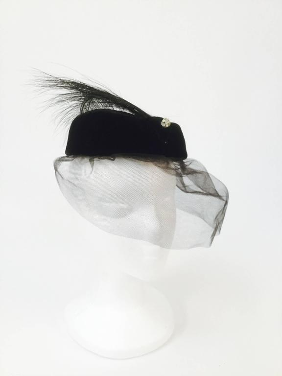 Elegant Miss Sally Victor pillbox hat! This velvet pillbox hat features a small triangular patch at the front, accented with a delicate rhinestone cluster sphere.  Four burnt ostrich feathers spring from beneath the velvet triangle, resting over