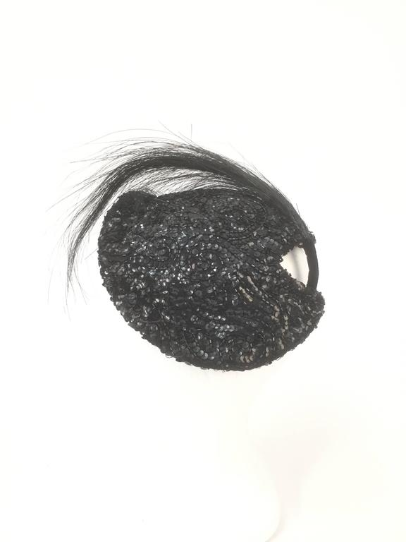 Stunning and glistening, this gorgeous Milgrim hat is sequined and beaded in a swirl of forms. The hat features a bouquet of burn ostrich feathers affixed to the hat via a velvet base. The hat has a mesh lining with a grosgrain ribbon, and sits