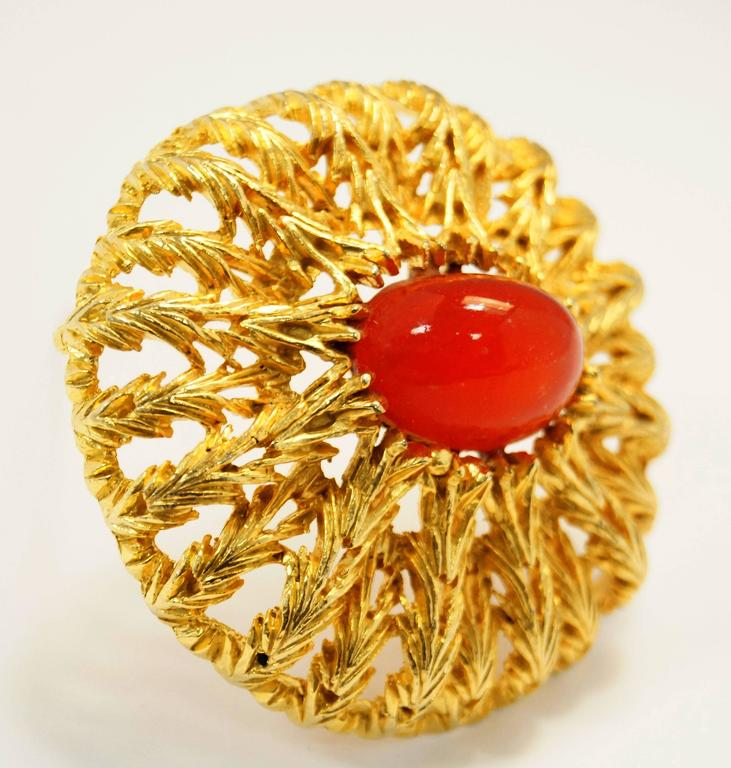 Absolutely show stopping vintage brooch by Elsa Schiaparelli! This brooch features an oval vermillion cabochon surrounded by organic chevron-shaped floral flourishes in a radial pattern, creating a gorgeous and ornate sunburst design.   *All