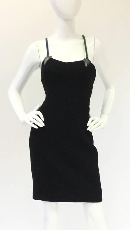 Bob Mackie does it again with this fantastically whimsical arrow strap dress! The back...the back...  This little black dress with a twist is mid-thigh length and has a subdued sweetheart necklinein front.  Walaa! the straps in back are