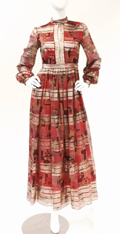 Gorgeous geometric print gown with  by Elinor Simmons for Malcolm Starr. This dress has a high collar with keyhole neckline, natural waistline ankle-length skirt, and voluminous shirtwaist sleeve. The geometric print features horizontal stripes