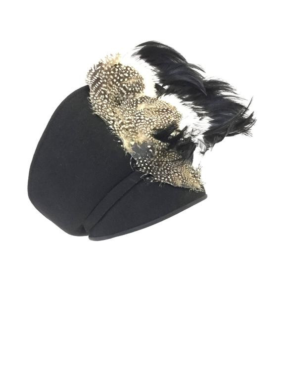 Absolutely striking hat by Jack McConnell boutique! This sculptural hat features a black felt base consisting of a rounded base that fits snuggly on the wearer's head, and a tiara-like brim. The upturned brim is richly ornamented with guinea fowl