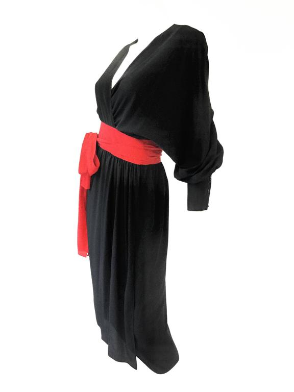 1970s Adele Simpson Black and Red Wrap Dress. Elegant and versatile wrap dress by Adele Simpson! This fantastic piece features voluminous bishop sleeves with button cuffs, and a dramatic red sash reminiscent of the Japanese obi, that is affixed to