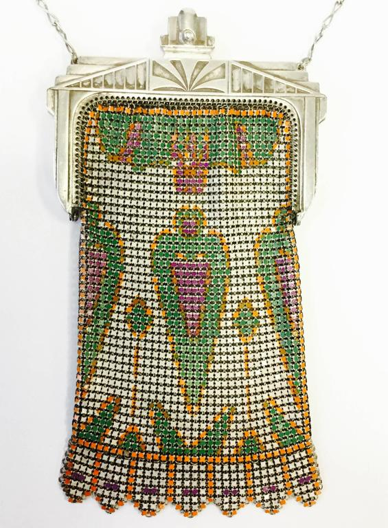 Fantastic 1920s mesh evening purse! This chainmail purse has a pressed metal art deco closure with a sunburst design, and the body features a wonderfully preserved enamel print. The symmetrical peach pink, parrot green, and tangerine orange