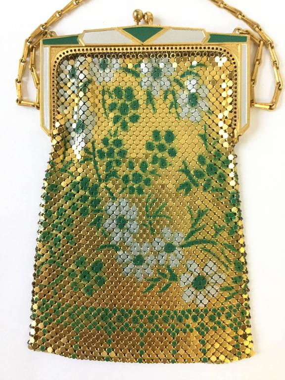 Glitzy and glamorous 1920s Whiting and Davis evening purse! This gorgeous enamel mesh purse features an art deco clasp painted in alternating white and green. The mesh body of the purse has a floral design consisting of sprigs of white and green