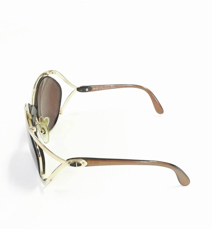 "Iconic 1980s Dior butterfly sunglasses! These glamorous, feminine sunglasses showcase Dior's famous butterfly design. The chocolate brown and gold-tone frames gently wrap around the oversized lenses. The letters ""CD,"" for Christian Dior,"