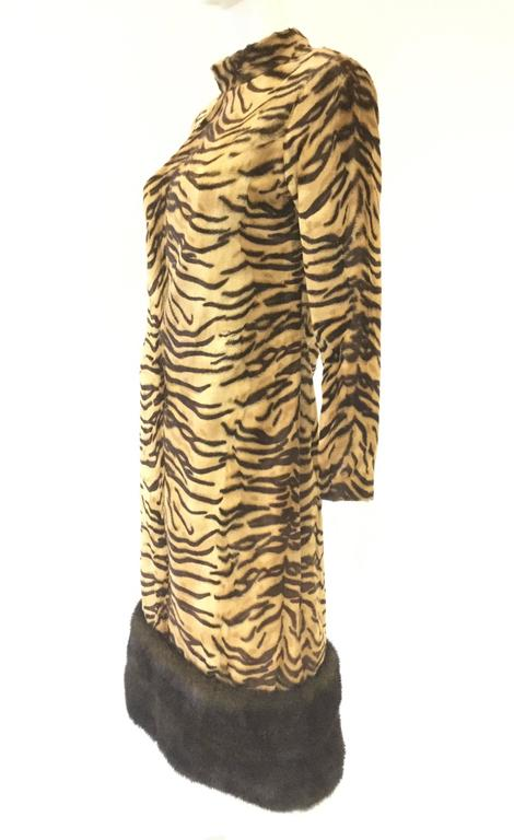 This striking dress made in France for I. Magnin and Co has long sleeves, a tall turtleneck collar, and hits just below the knee. The dress is composed of a fantastic medium length fur-like tiger stripe print fabric spanning the entirety of the