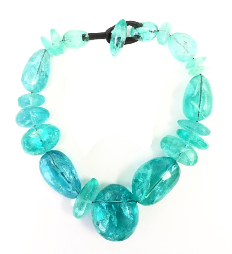 This gorgeous demi parure created by Gerda Lynnggaard for Nikoli Monies is composed of a set of earrings and a necklace, both made of the same incredible ice blue beads held together on a leather cord. The beads feature expertly molded rifts and