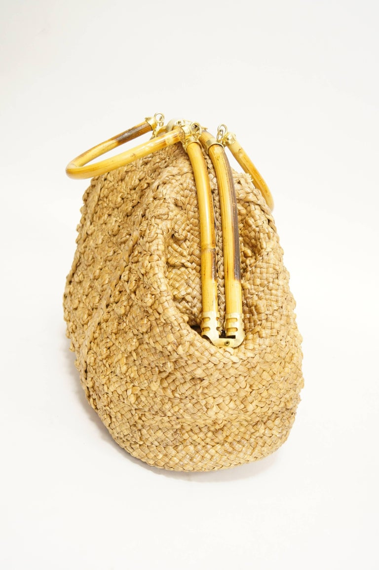 Sculptural hand woven bag by Delill! The bag is composed of woven grass carefully treated with resin, giving it a glossy shine and adding to its durability. The grass is woven in a criss-cross pattern, with accent knots and vertical stitching