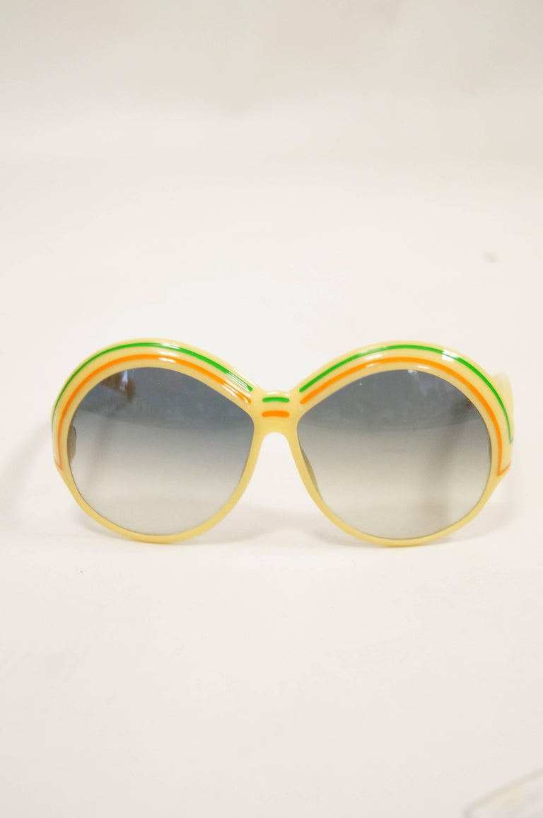 So vintage! So fabulous! Yellow frames with wide, circular lenses in a green ombre tone. Brow decorated with orange and green lines. Made in Germany.  Frame Width- 6