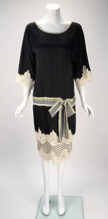 Beautiful, sweet, and fun Geoffrey Beene black dress. The dress is made of silk with alencon lace. Lovely kimono sleeves fall from the shift shaped bodice. The alecon lace trim dangles from both the sleeves and hem. The belt is made up of Navy blue