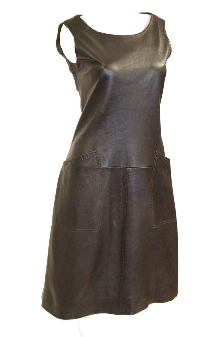 Buttery soft lambskin dress in espresso brown. The shift dress is knee length, sleeveless, and has a wide, round neckline. The dress features square pockets, with seams that blend into the waist structure of the dress. Wear with a white turtleneck