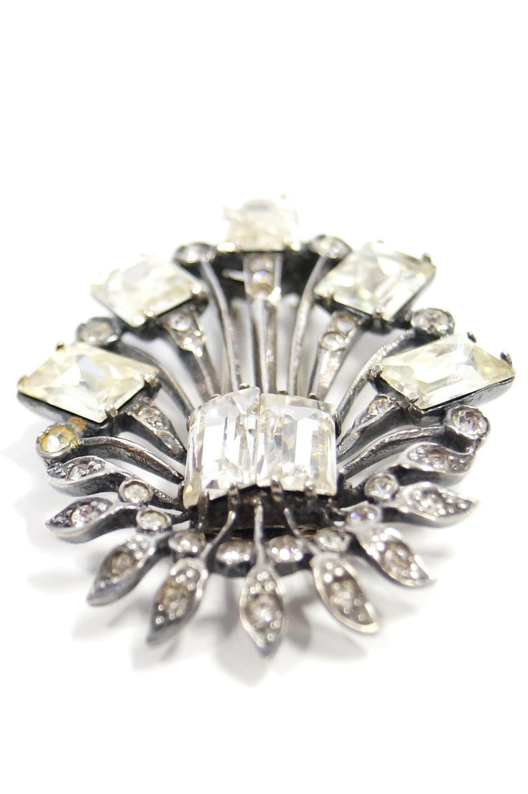 Elegant oversized sterling and rhinestone brooch by Eisenberg. The brooch consists of two large emerald cut clear rhinestones from which sprout various sterling stems. The longer stems are adorned with small round multifaceted rhinestones and are