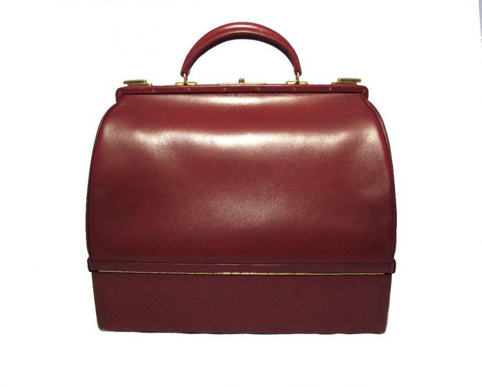 This rare Hermes Sac Mallette is in very good vintage condition.  The exterior features beautiful rouge red box calfskin leather trimmed with the signature gold Hermes hardware.  The top compartment opens through two slide latches and a push button