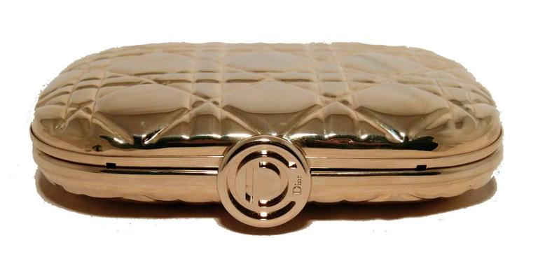 Fabulous Christian Dior gold metal evening bag in excellent condition.  Gold metal box form with signature cannage quilted pattern throughout.  Top lifting closure opens to a black leather lined interior with an attached hidden gold chain shoulder