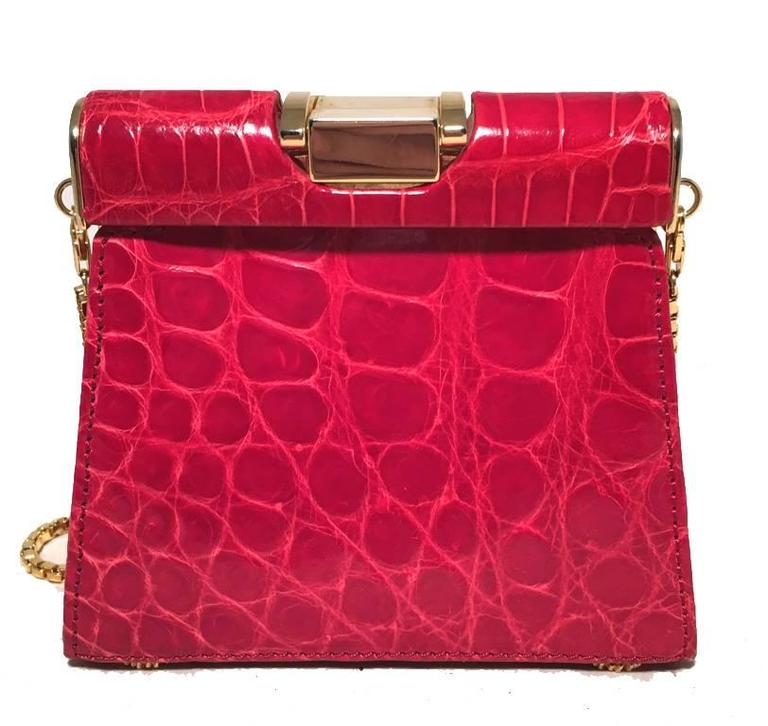 Beautiful Vintage Escada red alligator mini bag in excellent condition.  Bright red alligator leather exterior trimmed with gold hardware.  Chain shoulder strap can be removed to use this piece as a clutch.  Lifting top closure opens to a brown