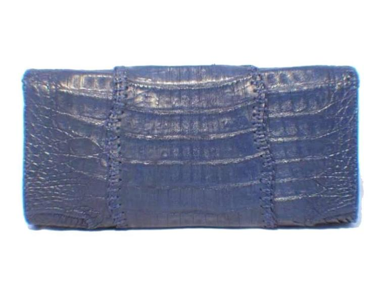 This simply stunning Carlos Falchi clutch is a must have for any collector's wardrobe. The exterior is in beautiful condition featuring patch worked blue crocodile leather that has been uniquely stitched together creating a gorgeous bohemian design.