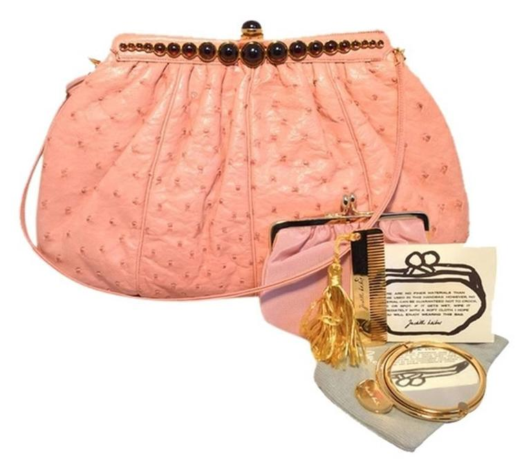 FABULOUS JUDITH LEIBER Pink ostrich leather clutch in excellent condition. Pink ostrich leather exterior with gold hardware and garnet type round stones along the top edge. Push button closure opens to a pink nylon lined interior that holds 1 slit