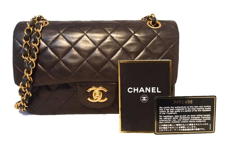 "Beautiful Authentic Chanel 9"" double flap classic in excellent condition.  Black brown lambskin leather exterior trimmed with gold hardware and signature woven chain and leather shoulder strap.  Front twist CC logo closure opens double flap style to"