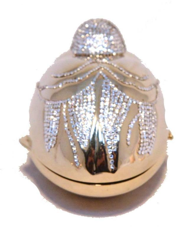 Beautiful Judith Leiber sitting duck minaudiere in very good vintage condition.  Gold sitting duck form with clear Swarovski crystal embellishments around the exterior. Side lifting closure opens to a gold leather lined interior that holds one side